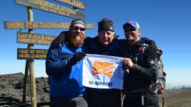 Three military veterans stand atop Mount Kilimanjaro