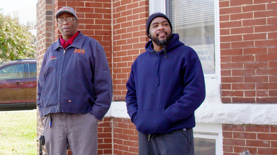 On a sunlit but cool day in Baltimore, David Anderson, in his pest-control work jacket and cap, and Devin Lee, in ski cap and blue fleece pullover, take a break to talk about life in their urban neighborhood.
