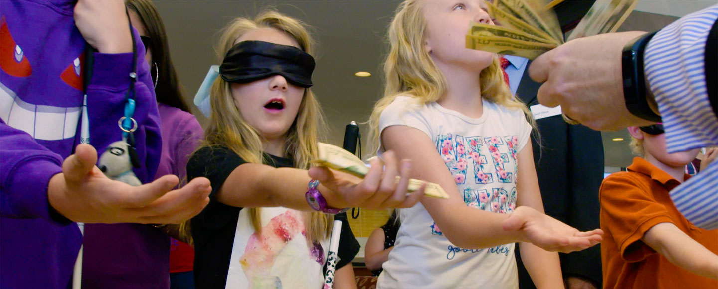 Students with blindfolds extend their hands as an adult places cash in their hands at the National Federation of the Blind's BELL Academy.