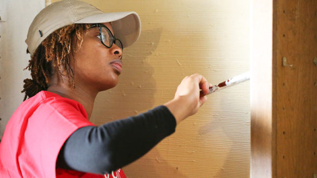 """Sharde Wilson adds a coat of paint. She hopes the home will bring """"joy"""" to Henline and his family."""