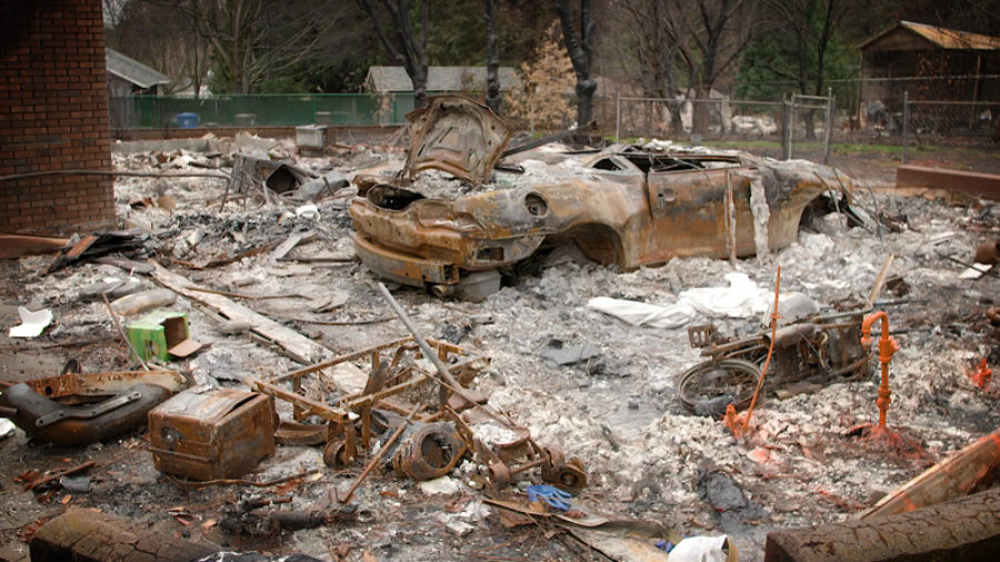 Photo of a burned-out car and debris in the yard of a home the Camp Fire destroyed in Paradise, California.