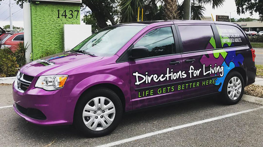 A purple van is parked in a parking lot. 'Directions for Living, Life gets better here.' is written on the side along with images of puzzle pieces.