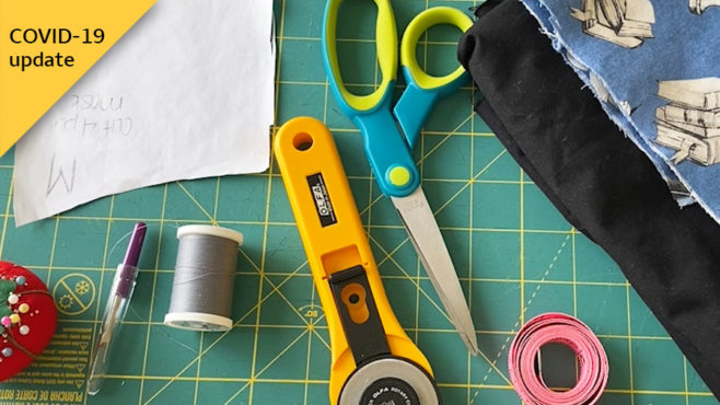 Sewing supplies, including a pin cushion, scissors, measuring tape, thread, pattern, fabric, and coffee filter, are spread out on a green gridded cutting mat.