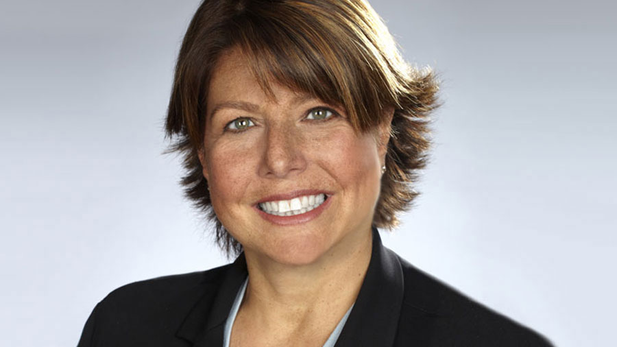 Jamie Moldafsky wears a black blazer against a grey background and is smiling.