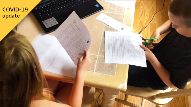 Two kids are holding worksheets as they sit at a table in front of a laptop. The boy cuts his paper. In the corner is a COVID-19 update graphic.