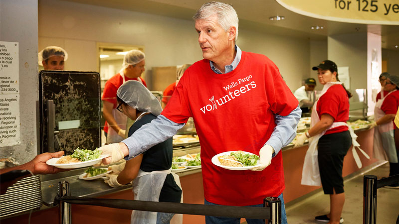 CEO Tim Sloan wearing a red shirt with Wells Fargo volunteers on it and holding two plates with food on them. He is handing one to a person whose hand is seen.