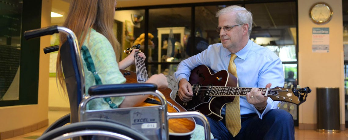 Ken Chinn of Wells Fargo Advisors plays guitar with Chloe Carroll after Chinn Guitar Project donation