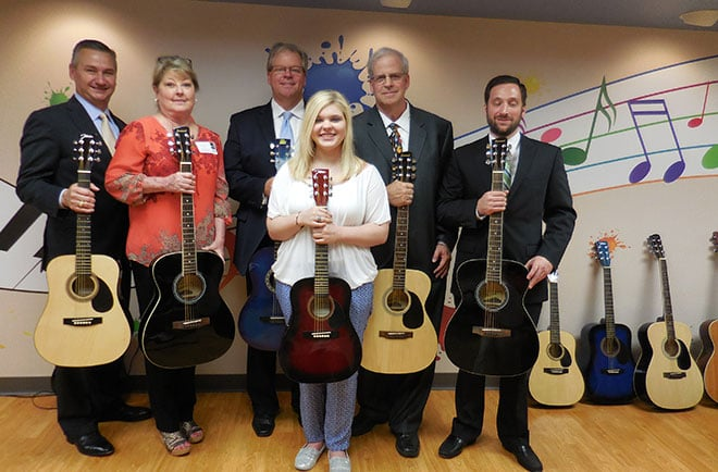 Greg Strnadel, Randy Halford, Bo Chinn, Tara Chinn, Ken Chinn, and Jonathan Killingsworth of Wells Fargo Advisors donate guitars to Children's Medical Center Dallas