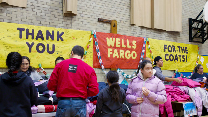 "Students and volunteers stand in front of a table full of coats in a school gymnasium. Signs on the wall say ""Thank You Wells Fargo For The Coats."""