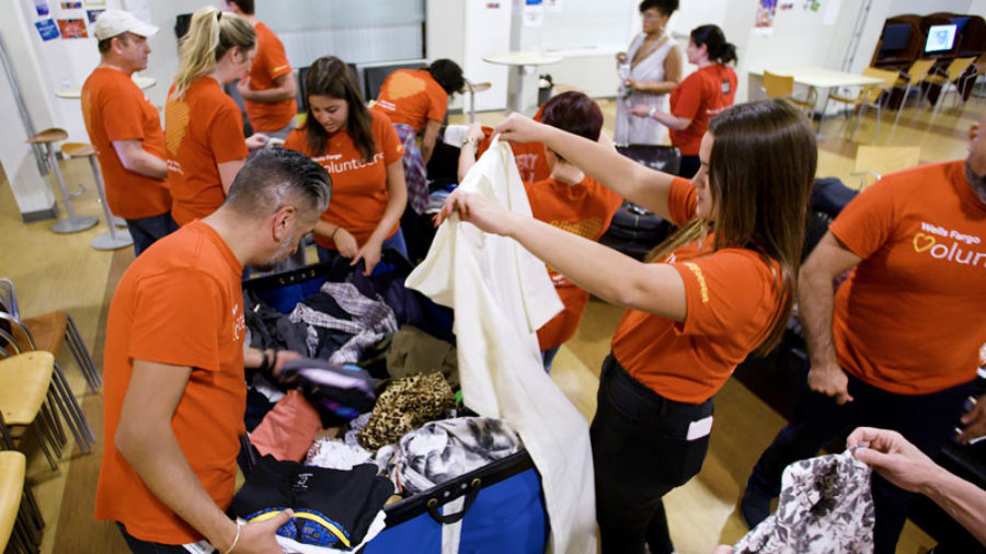 Team members wearing red T-shirts stand around a table sorting items of clothing.