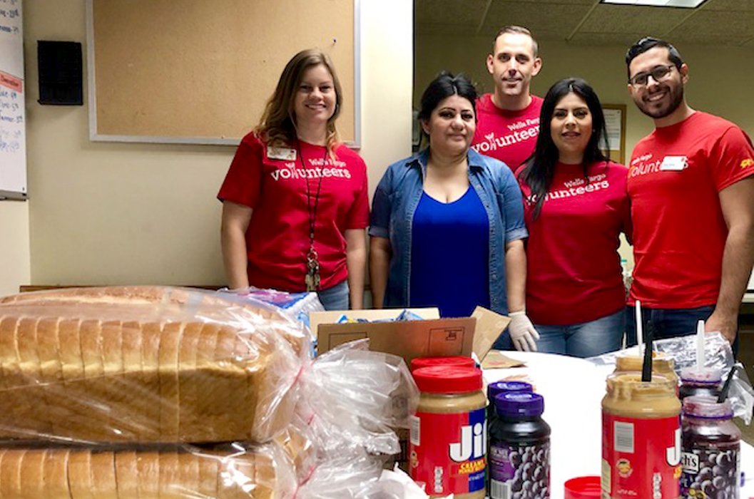 Three women and two men stand behind a table with bread, peanut butter, and jelly on it. Most of them wear red shirts.