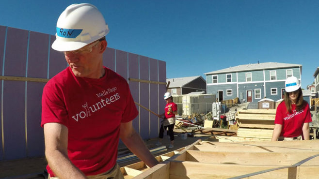 Story Type Indicator - video. A man wearing a red shirt with Wells Fargo volunteers and a white hard hat is carrying a wall of wood. To the right is a woman carrying another side. Behind them are houses and another person wearing a red shirt and white hard hat.