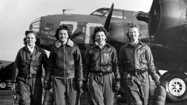 A black and white picture of four women in flight gear, wearing leather jackets and baggy pants, as they walk on a runway past military aircraft.