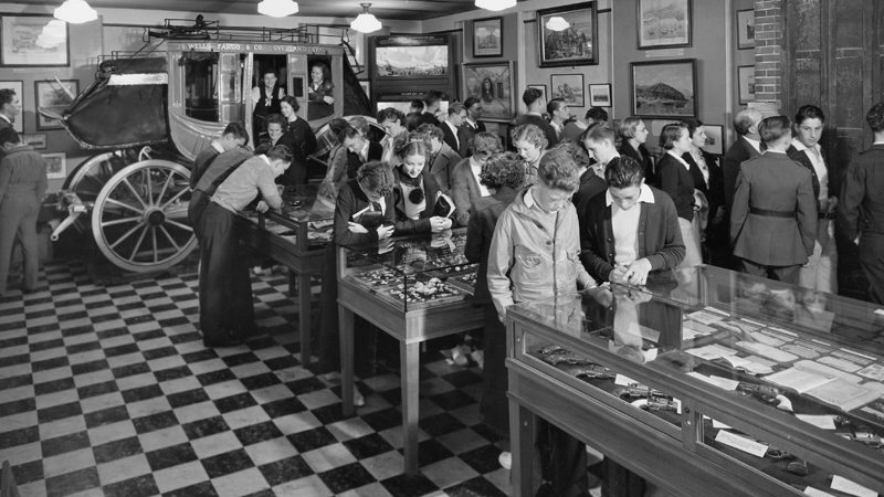 A black and white image shows a crowd of people standing to look at frames on the wall or looking down at tables with glass cases and items inside of them. At the back of the room is a stagecoach with two people inside.