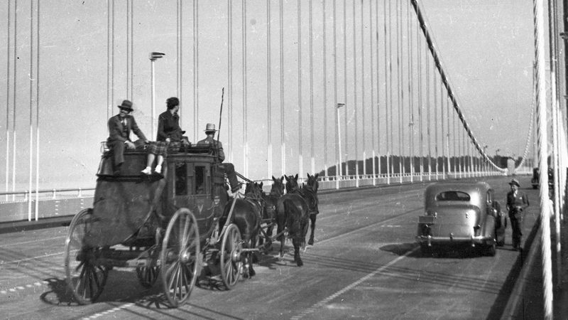 A black and white image shows a stagecoach with three people riding on top and four horses moving across a bridge. On the side of the road, a car is parked, and a man stands beside it.