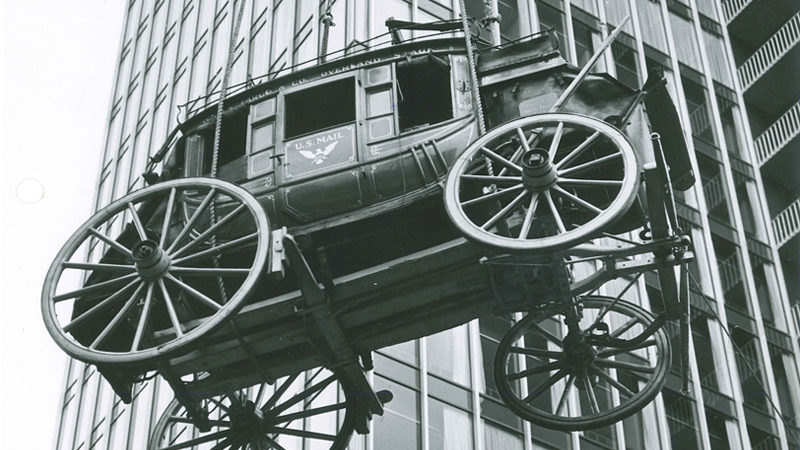 A black and white image is taken showing the bottom and side view of a stagecoach being lowered beside a building. The stagecoach has U.S. Mail written on the door.