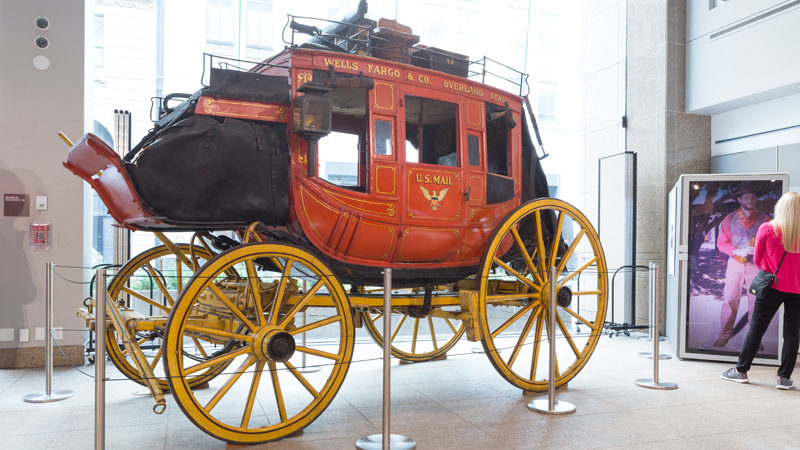 An image shows a red and gold stagecoach on display, with poles around it. To the right of it, a woman with her back to the camera is facing a large screen with a man on it.