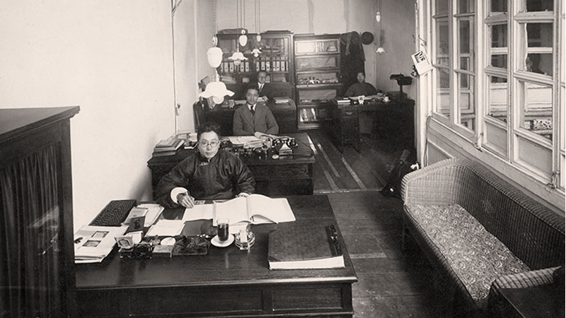 A black and white image shows the interior of an office with several desks in a row and one to the right of them in a corner. There are four men shown, each sitting at a desk and looking at the camera.