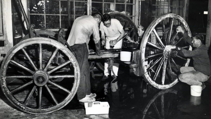 Four people with hand tools restore the wheels and carriage of a stagecoach.