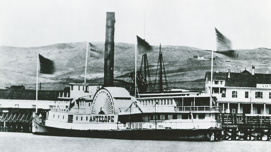 A black and white photo shows a large ship docked at a wharf with the bow pointed to left. The name Antelope is prominent on its paddlewheel on the port side. Hills are in the background, and the wharf building is to the right.