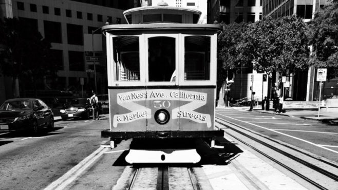 A black and white image shows the front of a cable car on a track in the middle of a street. Cars and buildings are on both sides of the street.