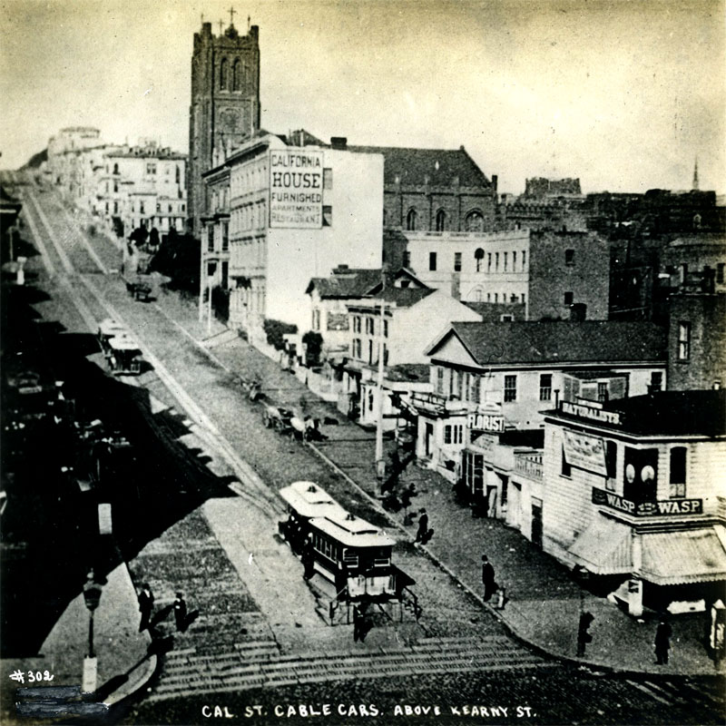A black and white photograph of a cable car about to go up a hill in an area with people on the street and buildings to the right.