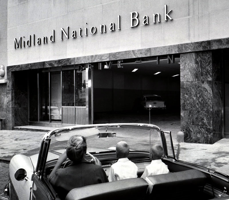 A black-and-white photo taken from behind a car with a woman and two young boys sitting up front as they drive toward a building labeled Midland National Bank.