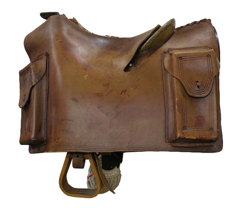 A photograph shows an aged, brown leather saddle. It has two pockets on the side and a stirrup.