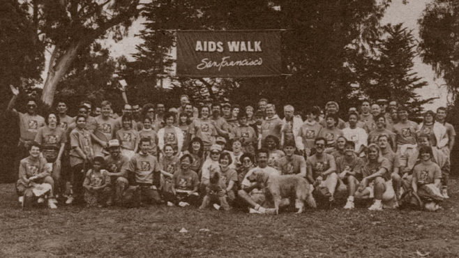 A 1991 photo of a large crowd of people gathered outside under a banner that reads AIDS Walk San Francisco.