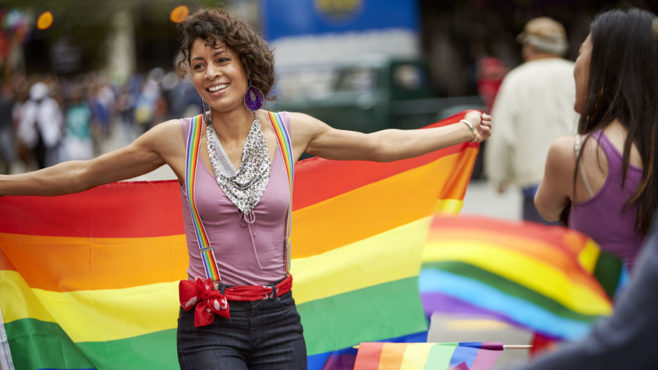 A woman smiles off camera as she holds a rainbow flag behind her.