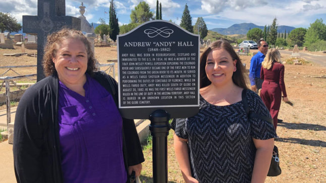 "Amanda Walters and Rochelle Mattingly stand on either side of a dark plaque on top of a dark pole. At the top of the plaque it says: Andrew ""Andy"" Hall."