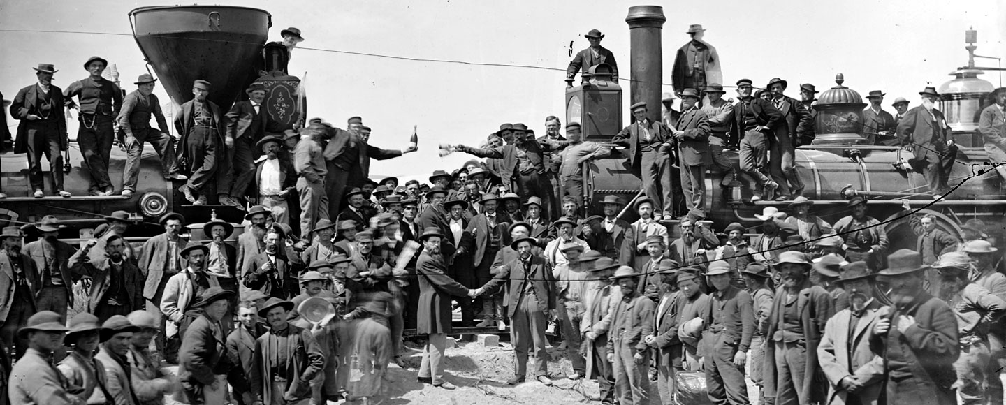 Large group of men gathered in front of two steam locomotives, which face each other on a single track, nearly touching. Leaning out over the fronts of the locomotives are two men holding champagne bottles, while two men shake hands front and center
