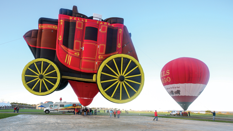 An image shows two hot air balloons on the ground in a large field where there are people standing nearby. The balloon on the left is red with black and yellow and is in the shape of a stagecoach. The balloon on the right is red with a white stripe.