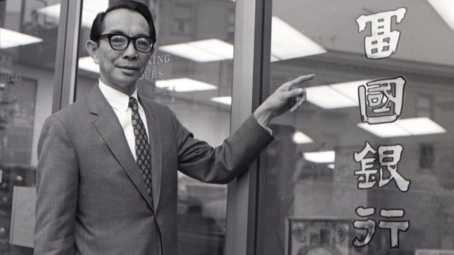 Wells Fargo Bank Manager Lyman Jang stands with the Chinese characters he chose to represent the bank in 1971.