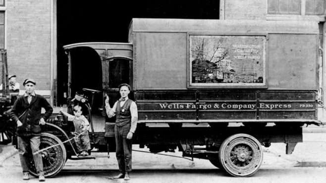 A black and white photo with two men and a young boy posing in front of a service truck with a Washington, D.C., wagon banner on the side in a frame.