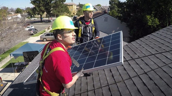 Two Wells Fargo team members wearing yellow hard hats are walking on the roof of a home carrying a solar panel.