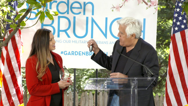 Standing on stage between two American flags, Jay Leno, right, presents vehicle keys to Angela Morales-Biggs. A sign that says Garden Brunch hangs behind them.