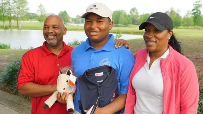 Teen golfer Kobe Narcisse in blue shirt and white cap holds a black Wells Fargo Championship golf shirt and plush pony. His dad, Robert, stands at left in a red golf shirt. At right is his mom, Keela, in black hat, white shirt, and pink jacket.