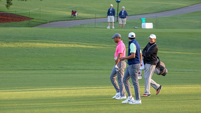 "Tiger Woods and Shahbaz and Ahmed Hashmi walk down hole No. 1 at the 2018 Wells Fargo Championship pro-am in Charlotte, North Carolina. Shahbaz Hashmi called Woods his ""golf idol."""