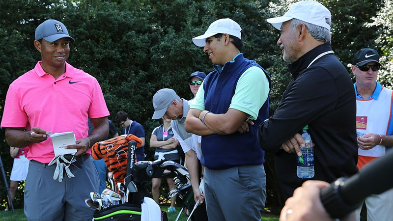 Tiger Woods shares a golf tip with Shahbaz Hashmi and his dad, Ahmed, during the 2018 Wells Fargo Championship pro-am.