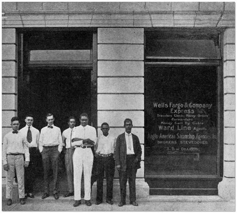 A black-and-white photo of seven men standing outside a building with Wells Fargo & Company Express on the window beside them.