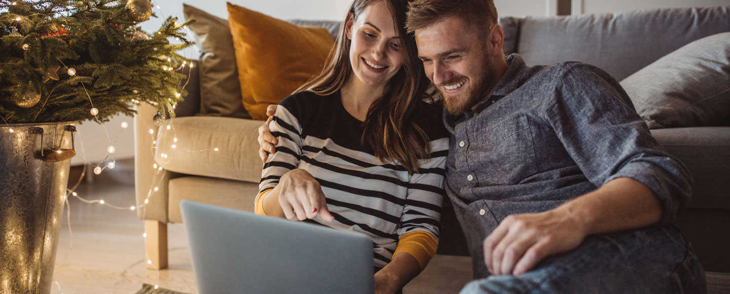 A woman and man sit in front of a couch while looking and smiling at a laptop that the woman is holding.