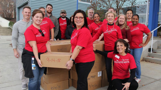 Wells Fargo volunteers with some of the 16,000 meals they prepared and boxed to feed students over the 2017 holiday break