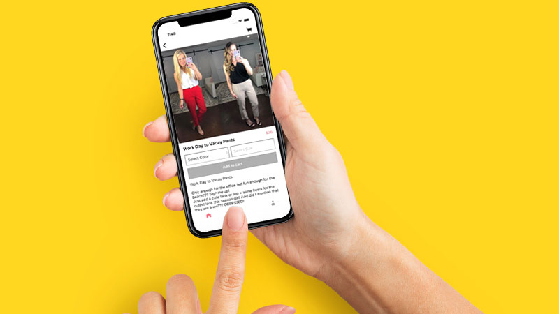A close-up shot of someone holding a smart phone with the Jules & James app on the screen, showing two women modeling clothing.