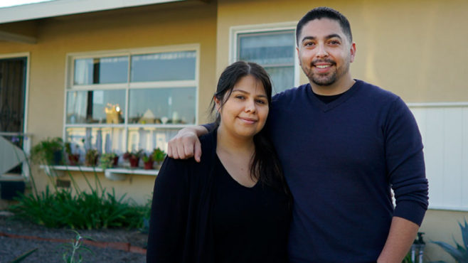 Siblings Kenneth and Leah Martinez stand together in the front yard of their new house.