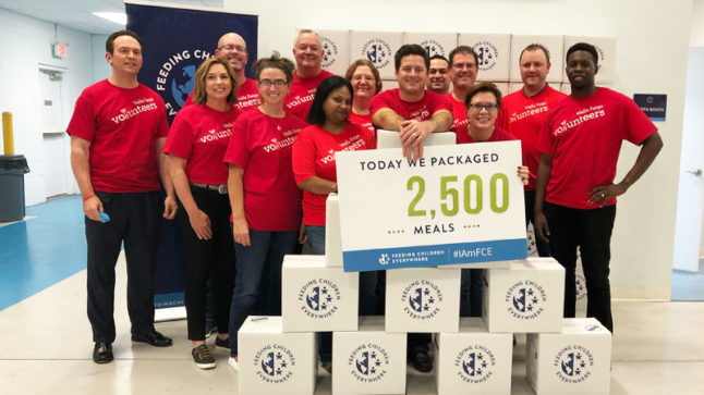 """Paul Richards and the Wells Fargo Commercial Banking team in Orlando in red Wells Fargo Volunteers T-shirts and completed meal kits holding the """"Today we packaged 2,500 meals"""" sign at the Feeding Children Everywhere warehouse in Longwood, Florida."""