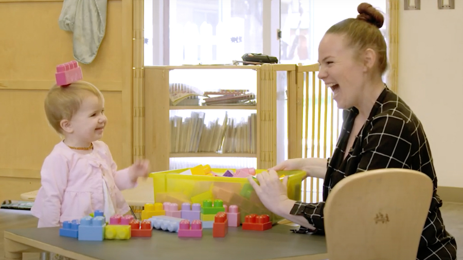 A woman and toddler girl sit at a table with colorful blocks on it. The woman smiles at the girl who has one of the blocks on her head and is smiling.
