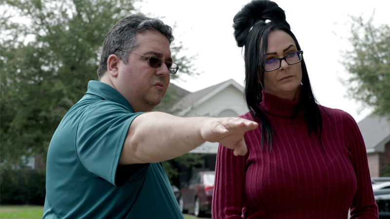 Andy Cordova is wearing a blue shirt and is pointing in the distance while talking to Bridgette Fletcher, who is wearing a long-sleeved maroon shirt.