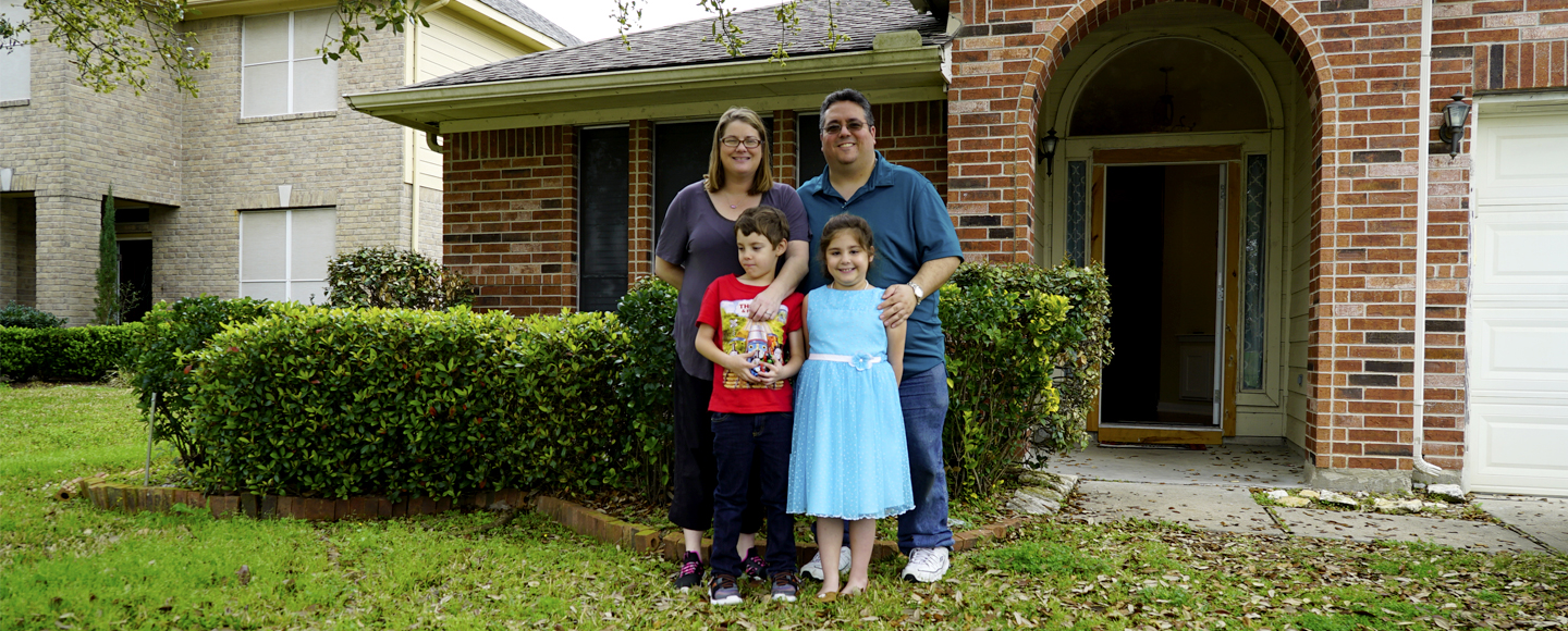 Andy and Sheri Cordova stand with their young children Jacob and Jordan, in front of their red brick suburban Houston home, which was restored after it was flooded during Hurricane Harvey in September 2017.