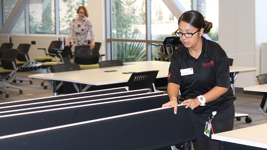 Selena Soltero handling folded tables in the Wells Fargo Connections facility in Chandler, Arizona.